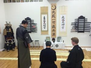 第七代宗家大塚龍之介(右)から允許された巻物の説明を受ける平田冨峰師範(中央)と、それを眺める第六代宗家大塚洋一郎(左)